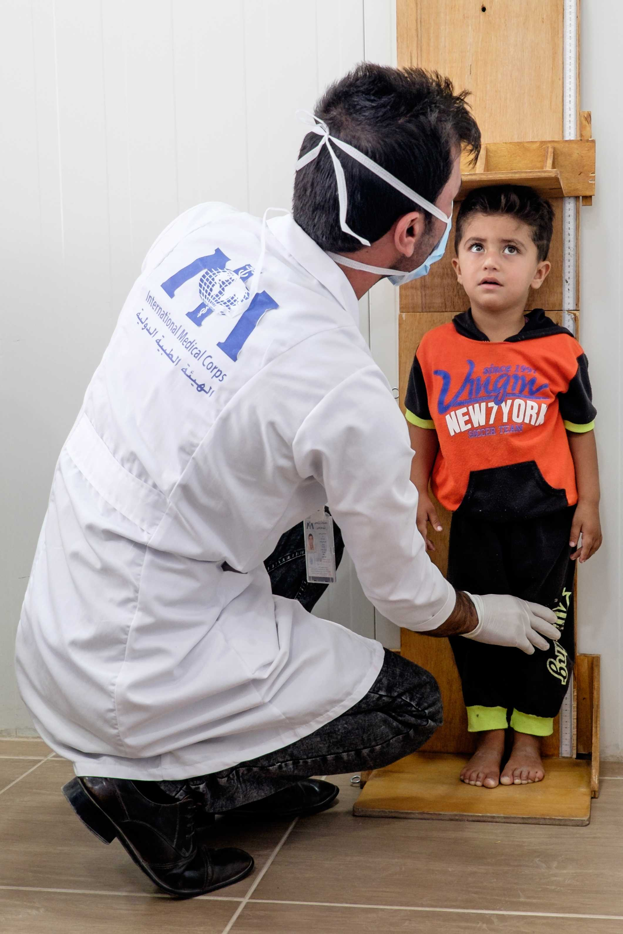 A young boy gets examined in the primary health care center inside the camp.